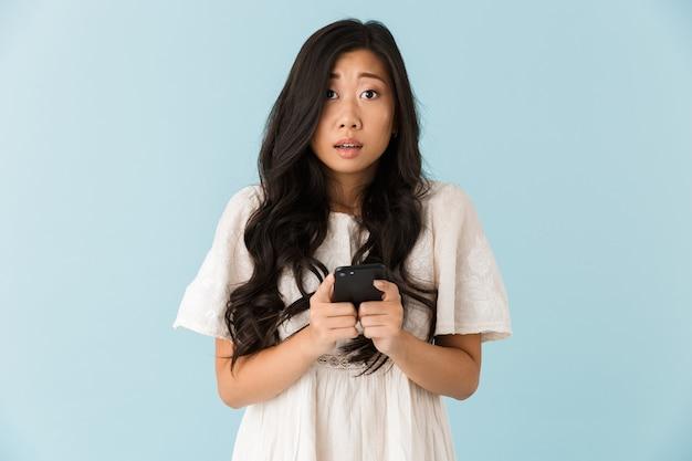 Bella donna asiatica impressionabile isolata sopra la parete blu facendo uso del telefono cellulare