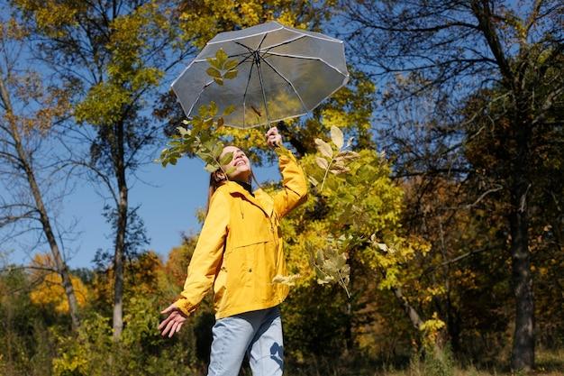 Donna attraente emotiva con ombrellone e foglie gialle alberi autunnali di sfondo felice