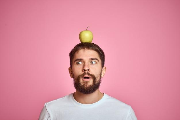 Uomo barbuto emotivo mela sulla t-shirt bianca testa ritagliata vista rosa