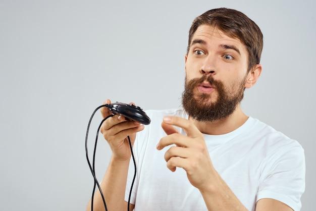 Uomo barbuto emotivo nella tecnologia t-shirt bianca joystick in mano giocando
