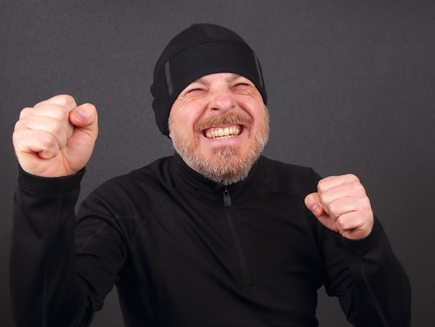 Uomo barbuto emotivo con le mani serrate alla ricerca della vittoria