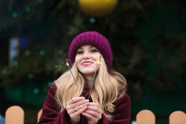 Modello biondo emozionale che tiene le luci di bengala incandescenti all'albero di natale principale a kiev. effetto sfocatura