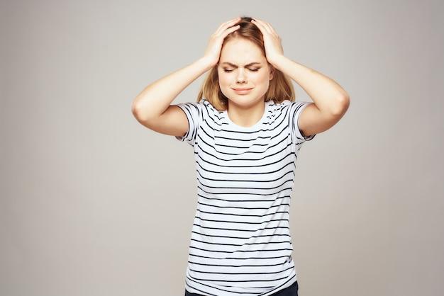 Donna bionda emotiva nell'espressione facciale di lifestyle di t-shirt a strisce.