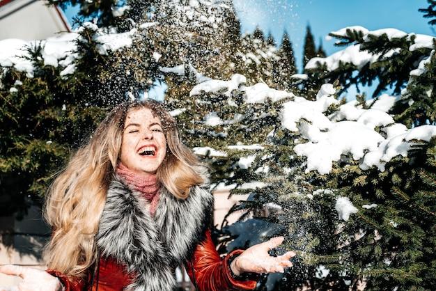 Emotiva ragazza dagli occhi azzurri che soffia neve nelle sue mani. gelido inverno.