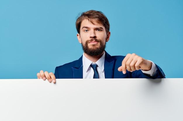 Emotivo uomo d'affari che spunta da dietro banner vista ritagliata parete blu copia spazio.