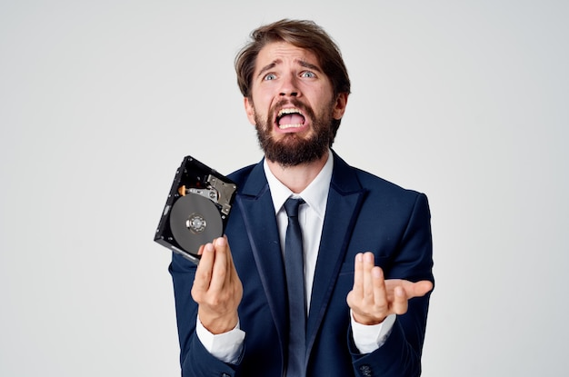 Uomo d'affari emotivo con disco rigido su tecnologia informatica