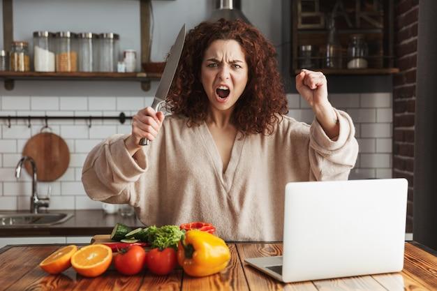Donna caucasica emotiva che usa il computer portatile e tiene il coltello durante la cottura di insalata di verdure fresche nell'interno della cucina a casa