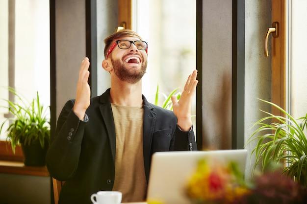 Emotional celebrating man at laptop