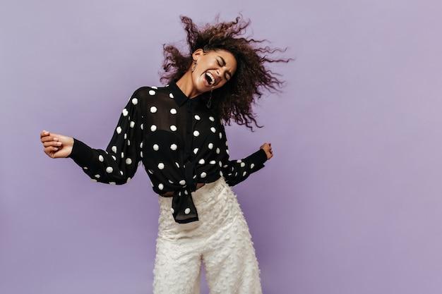 Ragazza fresca emotiva in camicia nera alla moda e pantaloni bianchi che gioca con i suoi capelli ricci e ride con gli occhi chiusi sul muro lilla