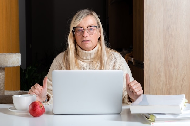 Donna freelance emotiva che lavora in ufficio a casa, sorpresa a fissare lo schermo del laptop scioccata
