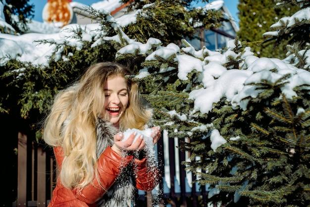 Ragazza emotiva che soffia neve nelle sue mani
