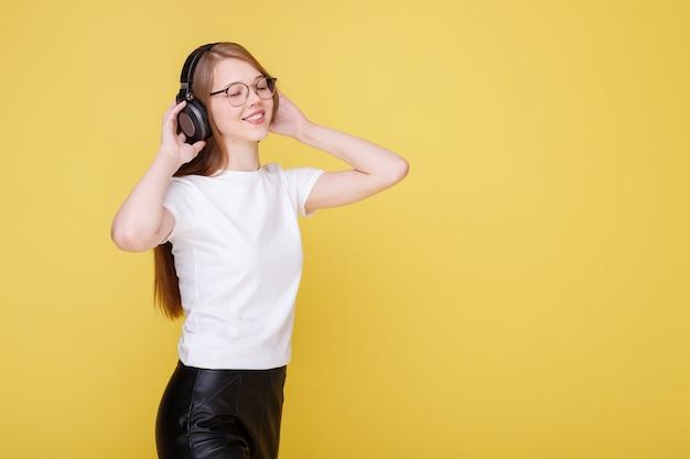 La ragazza emotiva ascolta la musica in cuffia e si diverte su una parete gialla