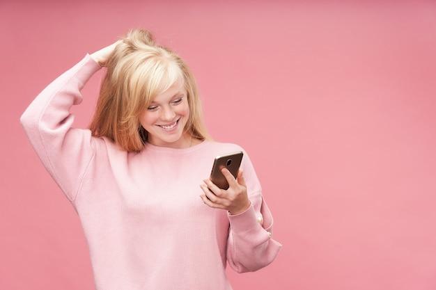 Ragazza emotiva guardando il telefono. la giovane bella bionda guarda ammirato lo smartphone che tiene la sua mano alla sua testa. felice ragazza teenager carina sorridente