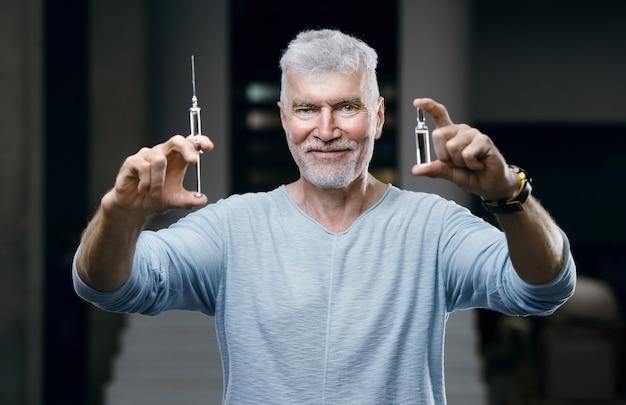 Emotivo un bell'uomo anziano dai capelli grigi vaccinato con una siringa in mano. immunizzazione e concetto di assistenza sanitaria