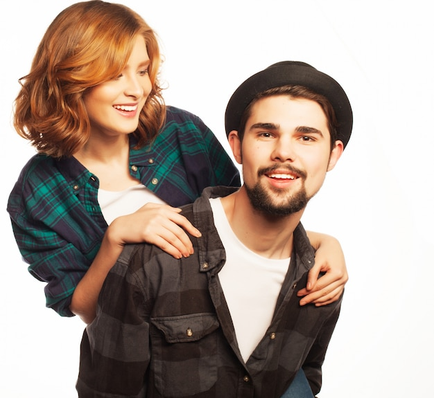 Concetto emotivo, di felicità e di persone: coppia di innamorati felici. giovane che trasporta sulle spalle la sua ragazza. sopra lo spazio bianco foto tonificanti alla moda speciali.
