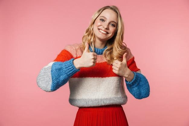 Emotiva felice giovane bella donna in posa isolata sul muro rosa fa i pollici in su