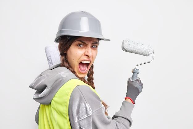 L'ingegnere industriale emotivo implementa il progetto di costruzione nella vita dipinge con urla di rulli che chiede con rabbia di non disturbarla mentre lavora indossa casco protettivo e uniforme. il miglior riparatore di sempre