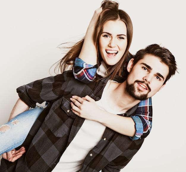 Emotivo, stile di vita, felicità e concetto di persone: felice coppia di innamorati. giovane che trasporta sulle spalle la sua ragazza. studio girato su sfondo bianco. foto tonificanti speciali alla moda.