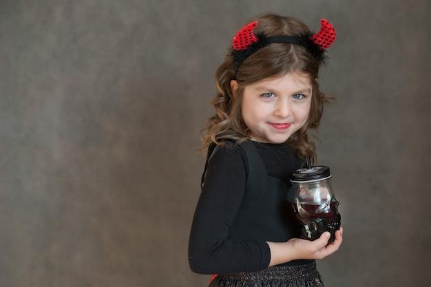 Bambina emotiva in costume di halloween e un bicchiere di sangue