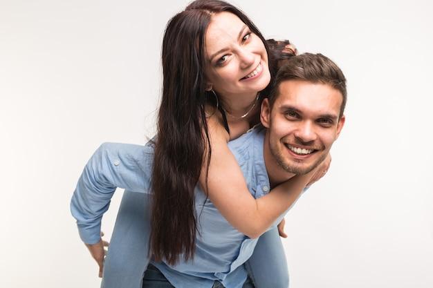 Emozionale, storia d'amore e concetto di persone - la giovane donna si è arrampicata sul ragazzo sulla schiena e sono felici e sorridono.