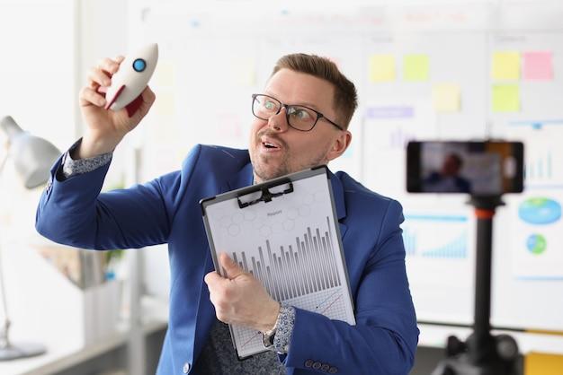 Il blogger maschio emotivo tiene in mano un razzo e conduce una formazione online sull'avvio rapido in