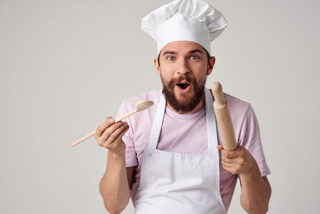 Lo chef maschio emotivo in un grembiule bianco sta provando il cibo