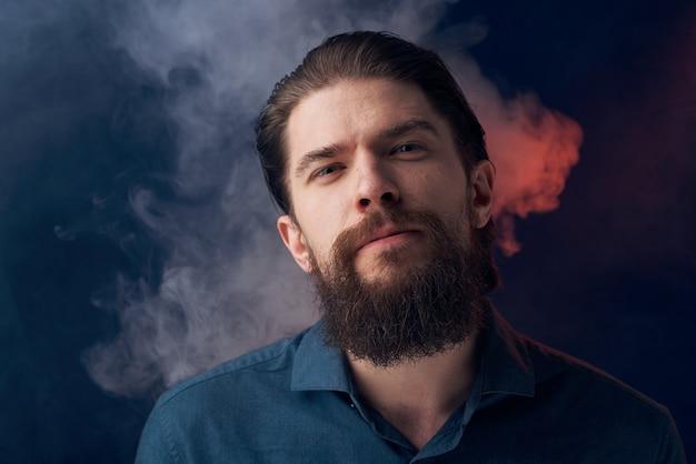 Emotivo uomo camicia nera sguardo attraente close-up fumo in background.