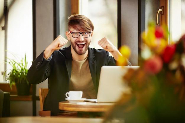 Emotional man celebrating at laptop