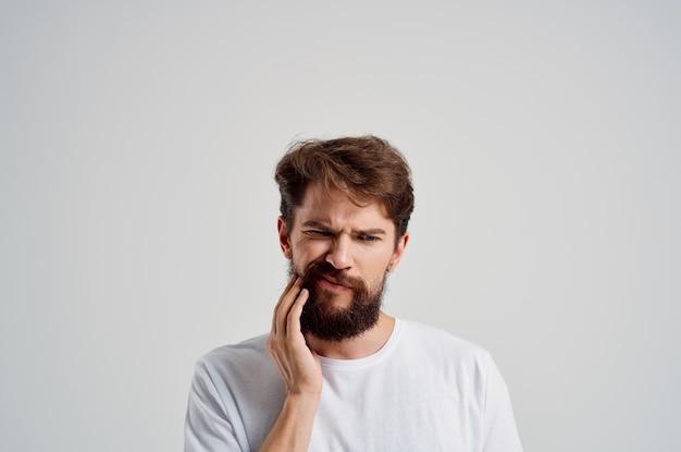 Uomo emotivo problema dentale trattamento odontoiatrico sfondo chiaro. foto di alta qualità