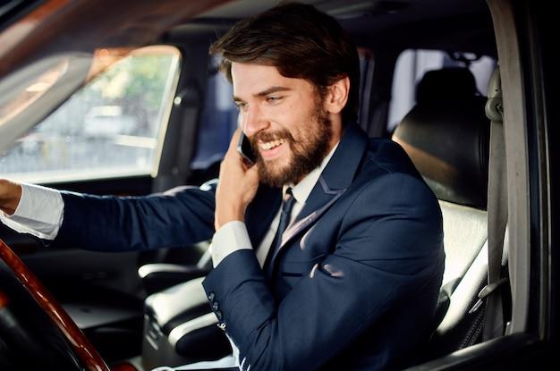 Uomo emotivo che guida una comunicazione di stile di vita di lusso in viaggio in auto per telefono