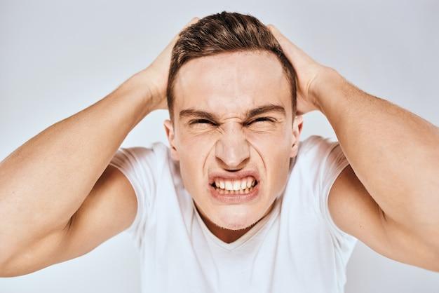 Uomo emotivo gesticolando con le mani dispiaciute di espressione facciale t-shirt bianca ritagliata
