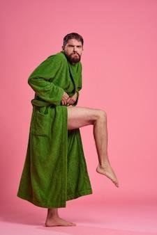 Un uomo emotivo in una veste verde in piena crescita su uno spazio rosa gesticola con le mani al