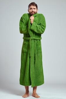 Uomo emotivo in una veste verde su grigio