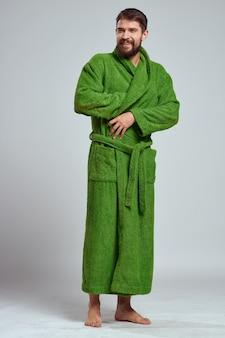 Uomo emotivo in una veste verde su una luce
