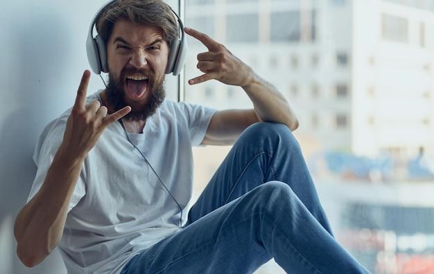 Uomo emotivo ascoltando musica in cuffia e gesticolando con le mani vicino alla finestra