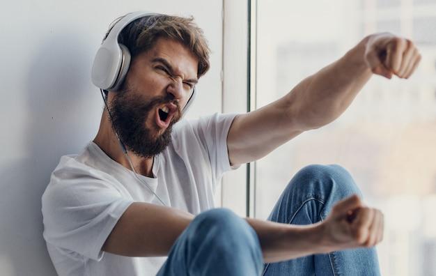 Uomo emotivo che ascolta la musica in cuffia e gesticola