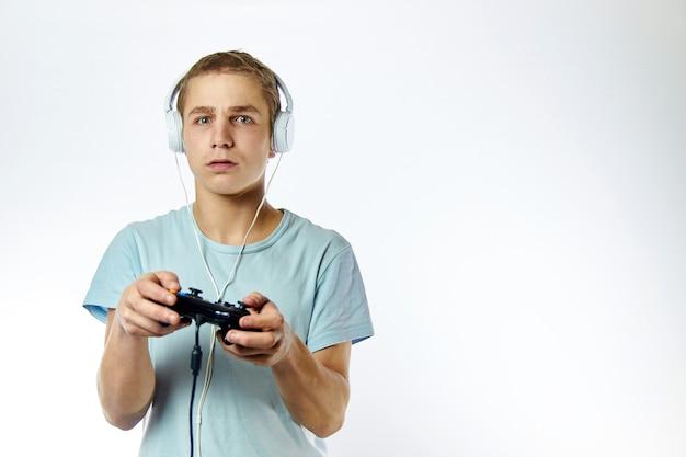 Uomo emotivo che gioca video gioco, con il joystick della console in mano su una parete leggera