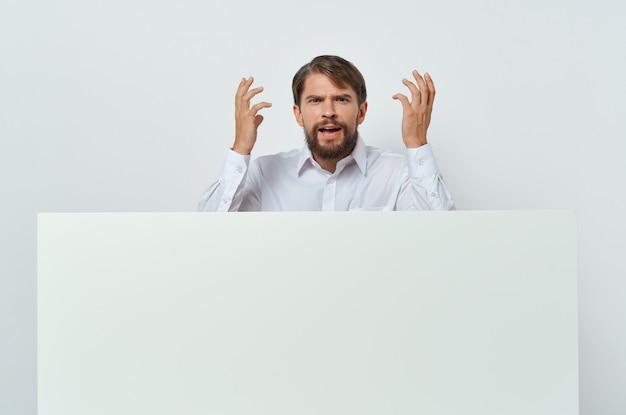 Uomo emotivo in camicia che gesturing con la sua pubblicità di affari di mockup bianco delle mani. foto di alta qualità