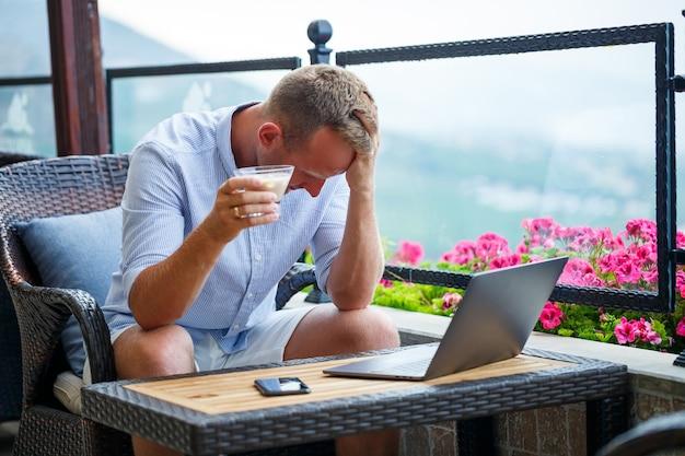 Un uomo emotivo si siede al computer in vacanza e lavora come libero professionista mentre è in vacanza