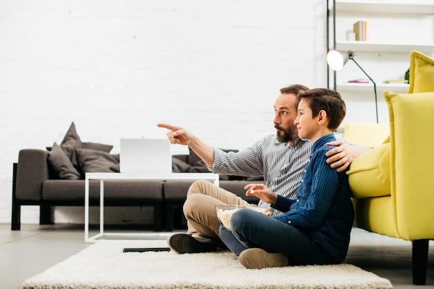 Uomo emotivo seduto sul morbido tappeto a casa con suo figlio felice e indicando lo schermo della tv mentre ragazzo allegro che mangia popcorn e sorridente