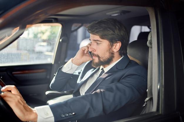 Uomo emotivo in giacca e cravatta in macchina un viaggio al lavoro comunicazione per telefono