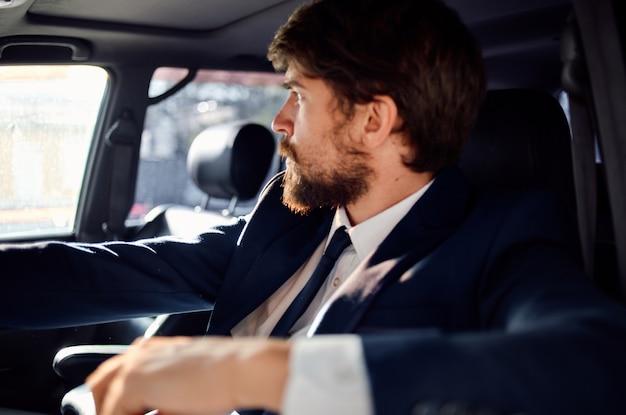 Uomo emotivo in giacca e cravatta in macchina un viaggio al lavoro fiducia in se stessi. foto di alta qualità