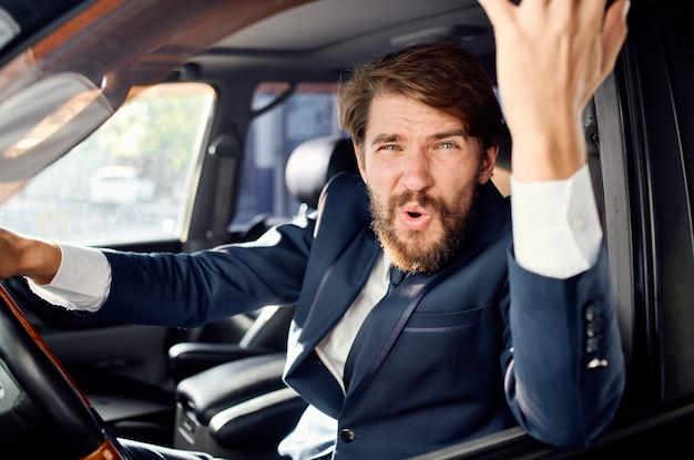 Uomo emotivo in giacca e cravatta in macchina un viaggio al servizio di lavoro