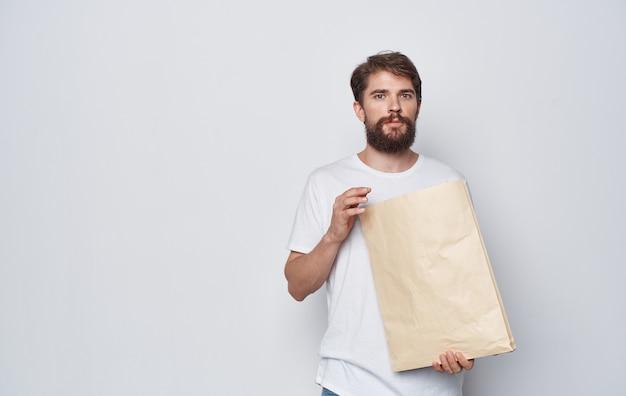 Uomo emotivo in una maglietta bianca con un pacchetto di artigianato nelle mani dello studio di emozioni isolato