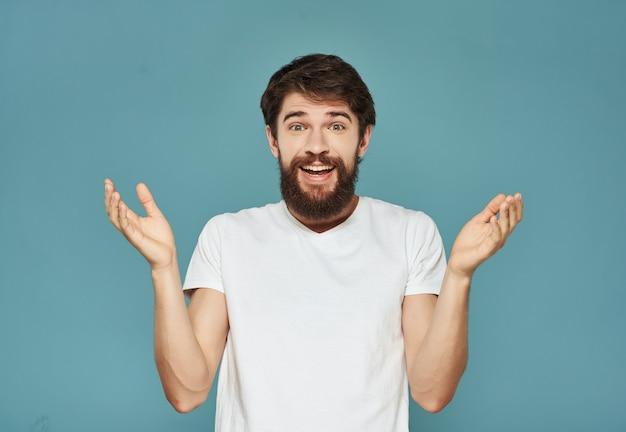 Uomo emotivo in una maglietta bianca dall'aspetto espressivo studio di malcontento