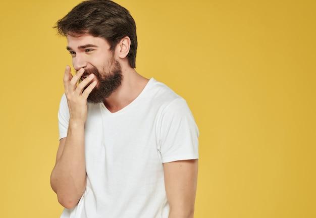 L'uomo emotivo con una maglietta bianca fa gesti di rabbia su sfondo giallo