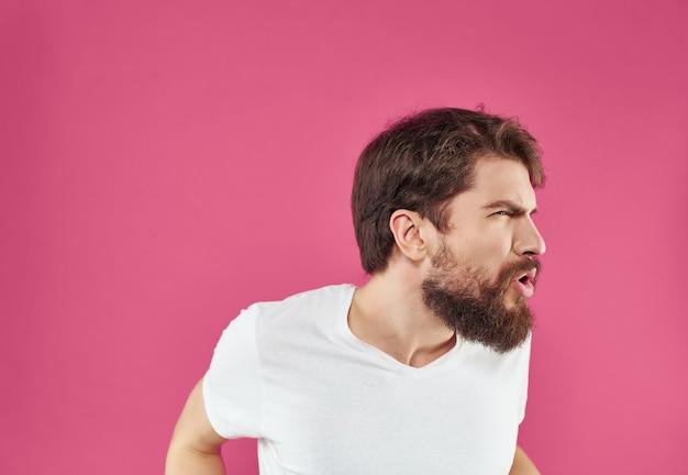 Uomo emotivo in uno studio di gesti delle mani di una maglietta bianca
