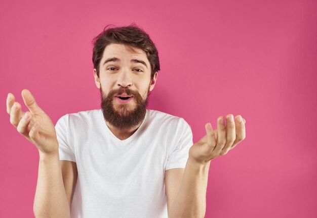 Uomo emotivo in una maglietta bianca felice espressione facciale sfondo rosa
