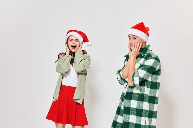 Uomo e donna emotivi in cappelli festosi si toccano il viso con le mani in uno spazio luminoso.