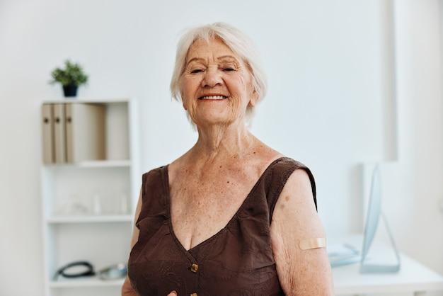 Anziana emotiva con cerotto sul passaporto del vaccino della spalla covid
